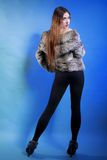 Young woman in fur long hair blue background Royalty Free Stock Images