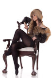 Young woman in fur  sit on armchair. Royalty Free Stock Image