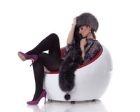 Young woman in fur  sit on armchair. Stock Image