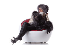 Young woman in fur sit on armchair Stock Photo