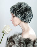 The young woman in fur and with a white rose Stock Images