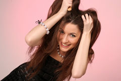 Young woman furiously scratches her tangled hair. Pink-gray background Stock Image