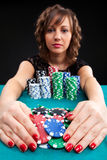 Young woman with gambling chips. Young woman holding gambling chips on black background stock photo