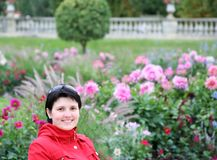 Young woman in a garden. Smiling happy young woman in a garden Royalty Free Stock Photography