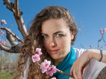 Young woman in garden. Girl in garden among the blossoming peach trees Royalty Free Stock Photos