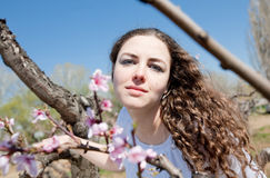 Young woman in garden. Girl in garden among the blossoming peach trees Royalty Free Stock Image