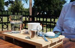Young woman in a garden restaurant with a glass of water, coffee stock photography