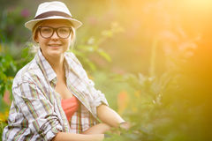 Young woman gardener in hat sitting next to plants Royalty Free Stock Images