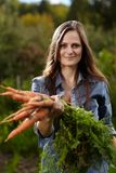 Young woman gardener holding a sheaf of carrots Royalty Free Stock Photos