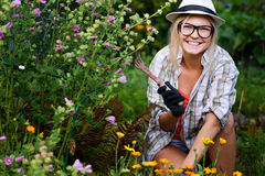 Young woman gardener sitting near flowers in garden holding hoe Royalty Free Stock Images