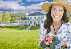 Young Woman Gardening in Front of Beautiful House Stock Photo