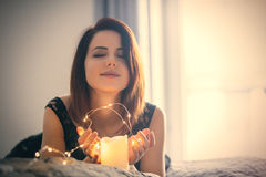 Young woman with garland and candle Stock Image