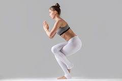 Young woman in Garudasana pose, grey studio background. Young attractive woman practicing yoga, standing in Eagle exercise, Garudasana pose, working out wearing Royalty Free Stock Image