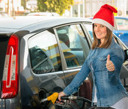 Young woman at gas station with Santa hat stock images
