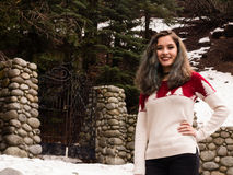Young woman by a gate in winter Royalty Free Stock Image