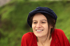 Young Woman in Gatsby Cap. Smiling young Caucasian woman with a blue gatsby cap in a park (Selective Focus, Focus on the left eye Stock Images