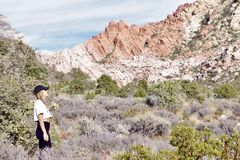 White Rock, Willow Springs, Red Rock Conservation Area, Nevada, USA. Young woman gazing at mountain range along the hiking trails on the White Rock Loop in stock image