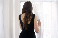 Young woman gazing out of window Stock Photos