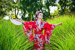 Young woman in geisha costume with a fan Royalty Free Stock Image
