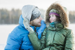 Young woman gently embracing her husband with on hand in winter frosty day Royalty Free Stock Images