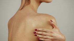 Young woman gently touching her shoulder, close up. Woman applying cream on her shoulder stock video