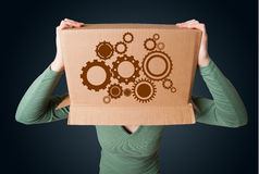 Young woman gesturing with a cardboard box on his head with spur. Young woman standing and gesturing with a cardboard box on his head with spur wheels royalty free stock photography