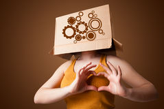 Young woman gesturing with a cardboard box on his head with spur Royalty Free Stock Images