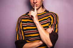 Young woman gesturing hush with her finger on her lip Stock Photo