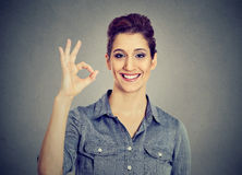 Young woman gesturing OK sign. Woman gesturing OK sign isolated on gray wall background Royalty Free Stock Images