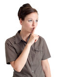 Young woman gesturing for quiet. Portrait of a young woman gesturing for quiet. Isolated over white background Stock Photos