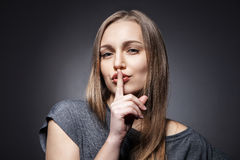 Young Woman Gesturing for Quiet or Shushing. Over dark grey background Stock Photo