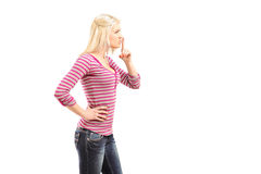 Young woman gesturing silence with finger over mouth. Isolated on white background Stock Photos