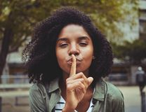 A young woman gesturing silence sign royalty free stock image