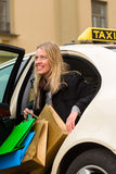Young woman gets out of taxi Stock Images