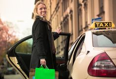 Young woman gets out of taxi carrying shopping bags. In hands Stock Photos