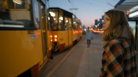 Young Woman Gets on the Yellow Tram at the Stop in the evening stock footage