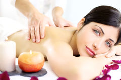 Young woman getting back massage in luxury spa Royalty Free Stock Photo