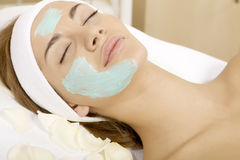 Young woman getting beauty skin mask treatment. On her face with brush Stock Photo