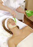 Young woman getting beauty skin mask treatment. On her face with brush Royalty Free Stock Images