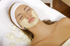 Young woman getting beauty skin mask treatment on her face with. Brush Royalty Free Stock Photo