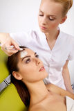 Young woman getting beauty skin mask treatment on her face with Stock Images