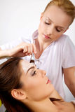 Young woman getting beauty skin mask treatment on her face with. Young women getting beauty skin mask treatment on her face with brush Royalty Free Stock Images
