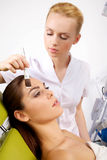 Young woman getting beauty skin mask treatment on her face with Royalty Free Stock Photo