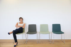 Young woman getting bored sitting in waiting room Stock Photography