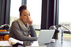Young woman getting bored while studying in library Stock Photography