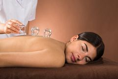 Young woman getting cupping treatment Stock Photo