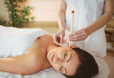 Young woman getting an ear candling treatment Royalty Free Stock Photo
