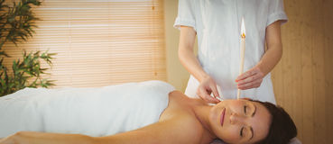 Young woman getting an ear candling treatment Stock Photos