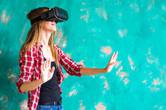 Young woman getting experience using VR-headset glasses of virtual reality much gesticulating hands Royalty Free Stock Photos