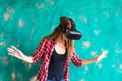 Young woman getting experience using VR-headset glasses of virtual reality much gesticulating hands Stock Photo